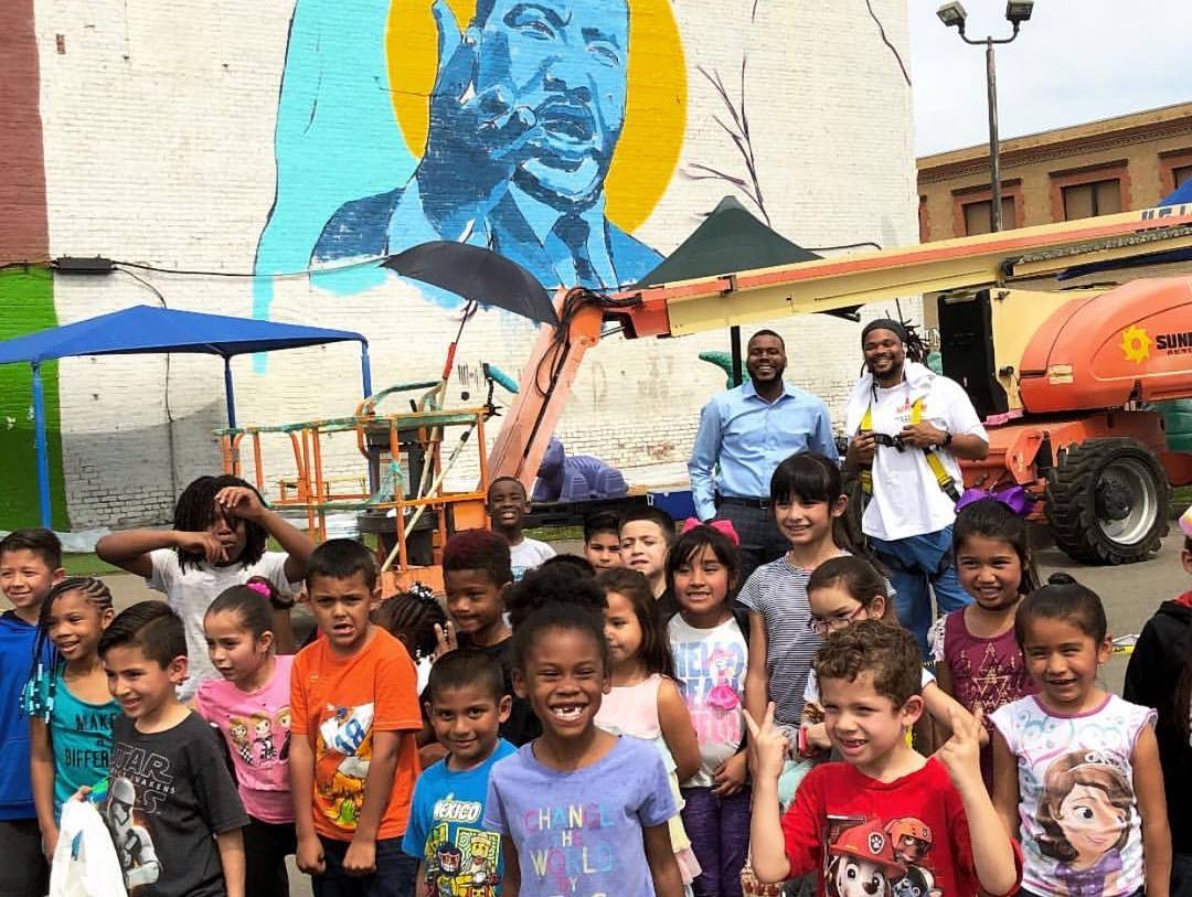 Gathering of people beneath mural of Rev. Martin Luther King