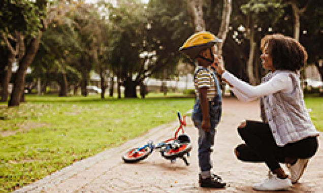 Adult fastens bicycle helmet on child