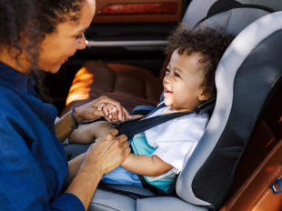 Adult buckles toddler into car safety seat
