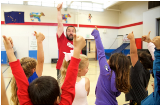 Image of coach and children in a gymnasium